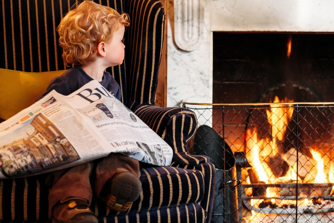 A young boy sits in a chair by a fire in a luxury family hotel