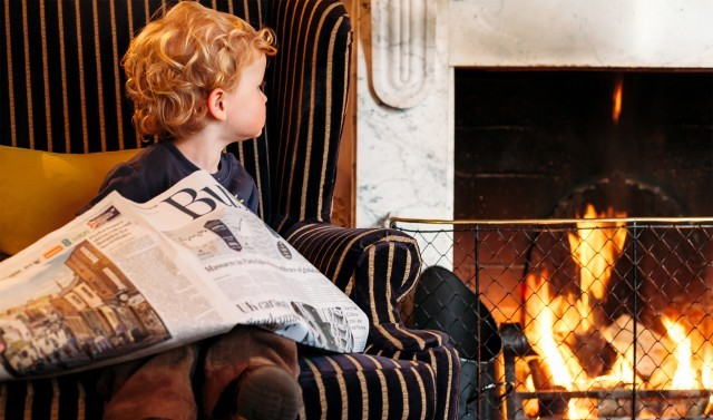 A young guest sits in an armchair at the fireside in a luxury family hotel