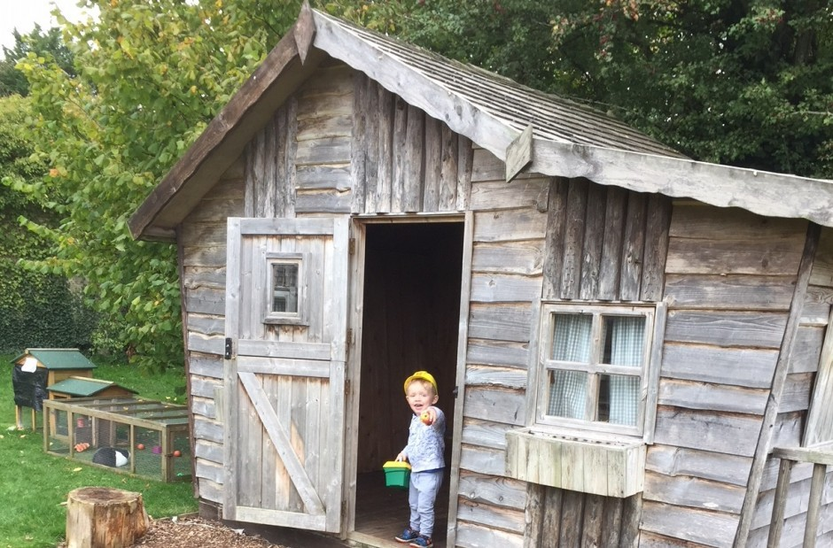 A child stands in a wooden shed at Woolley Grange hotel.
