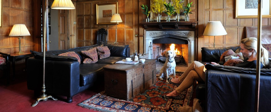 A guest and her dog sit in the Woolley Grange luxury family hotel lounge by the fire