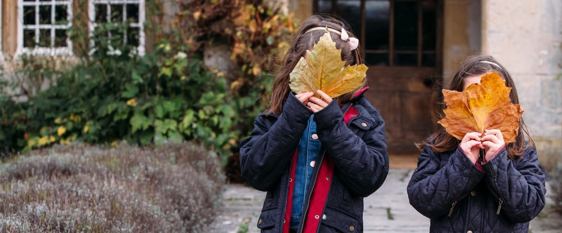 Two children hold autumn leaves at Woolley Grange luxury family hotel in Bradford on Avon