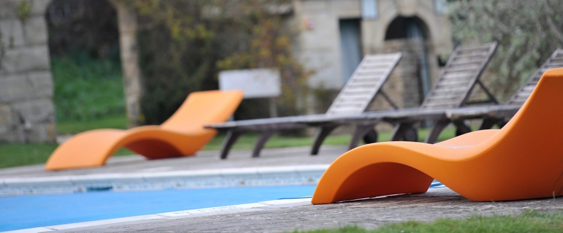 Loungers by the pool at the Woolley Grange Hotel spa in Wiltshire