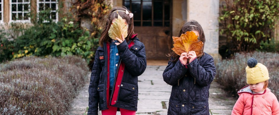 Children playing with autumn leaves outside Woolley Grange in Wiltshire