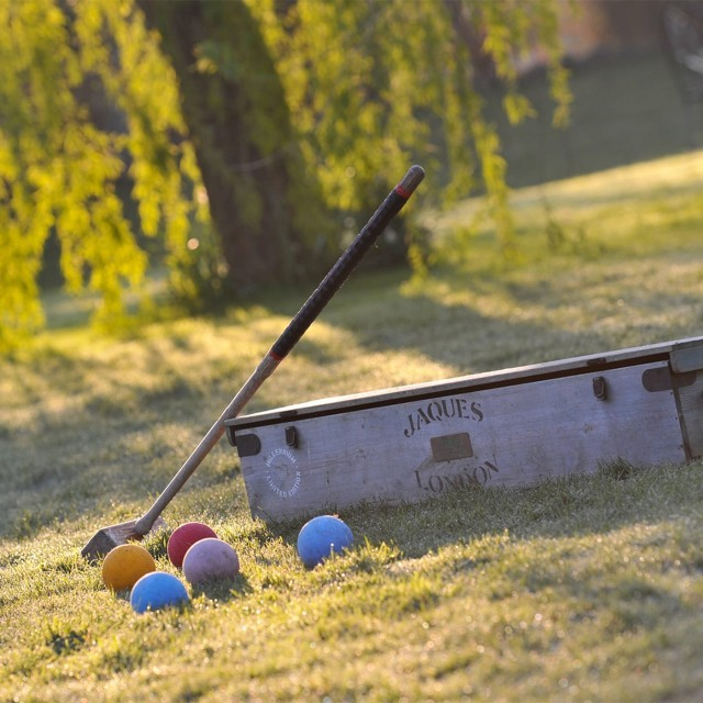 Croquet mallet and balls in the garden at Jacobean manor house Woolley Grange