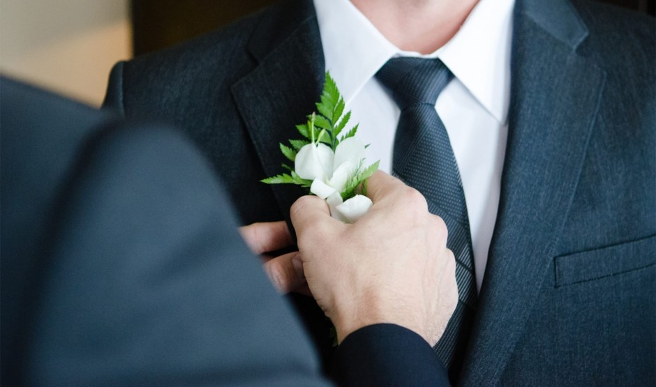A groom fixes a buttonhole at his Wiltshire wedding at Woolley Grange