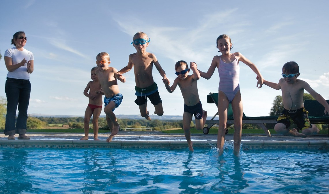Children jump into the outdoor swimming pool at Woolley Grange in Wiltshire