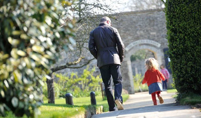 A father and child walk through the Woolley Grange gardens.