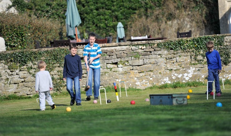 A family plays croquet in the grounds of the Woolley Grange Hotel near the Cotswolds