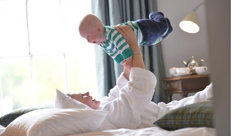 A mum lifts her child up in the air with a smile.